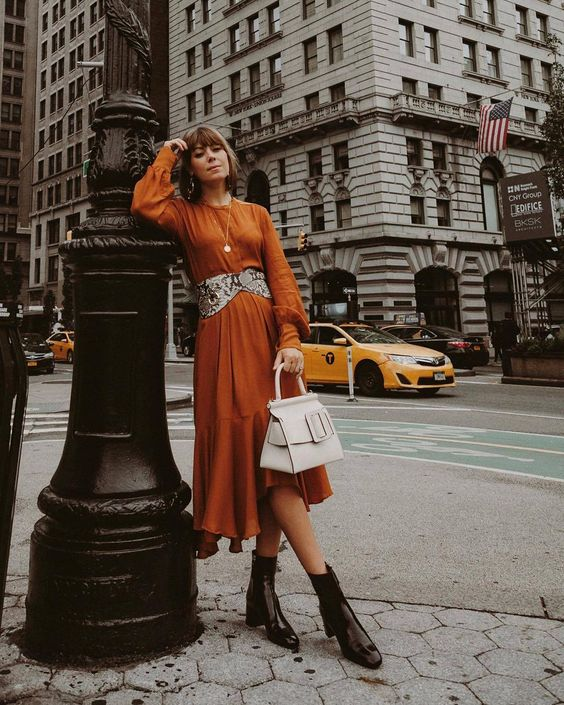 a rust-colored A-line midi dress with long sleeves, a snakeskin print belt, a white bag and black lacquer boots for the fall