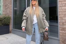 23 a white sweatshirt, an olive green oversized jacket, blue jeans, white trainers and a green cap