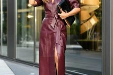 24 a purple leather midi dress with a front slit and short sleeves, black sock boots and a black clutch for a wow look