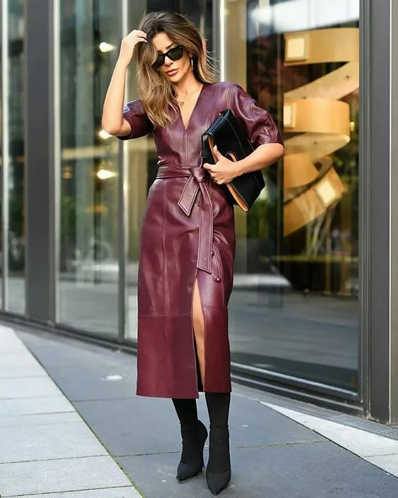 a purple leather midi dress with a front slit and short sleeves, black sock boots and a black clutch for a wow look