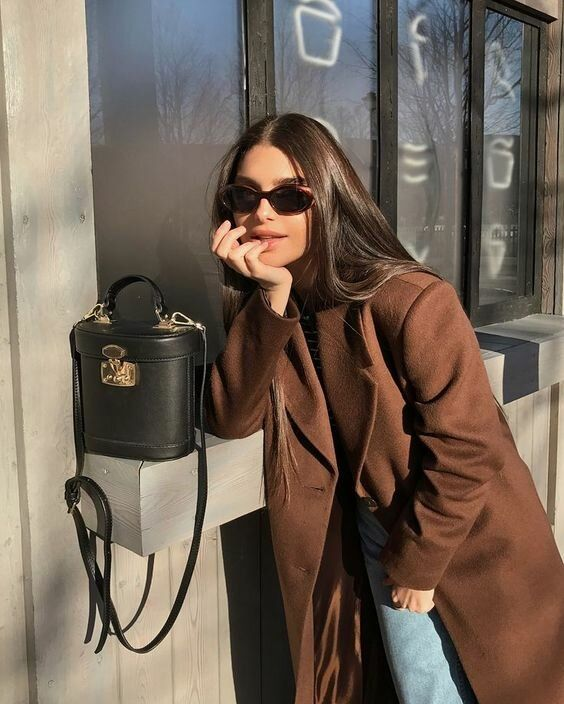 a simle and chic fall look with a brown jumper and a midi coat, light blue jeans, a black bucket bag