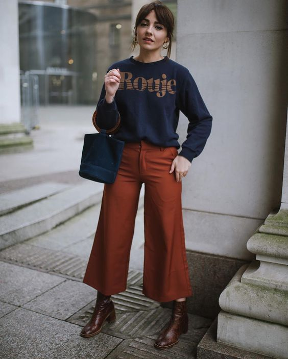 a simple and contrasting outfit with a navy printed sweatshirt, rust-colored flare trousers, brown boots and a navy bucket bag