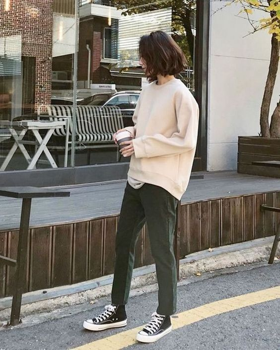 a white t-shirt, a creamy sweatshirt over it, dark green trousers, black sneakers for a simple and cool college look