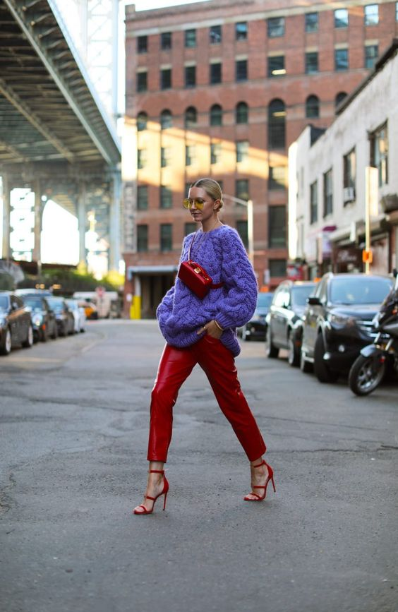 a maximalist fall outfit with a purple sweater, red leather pants and strappy heels, a red waist bag