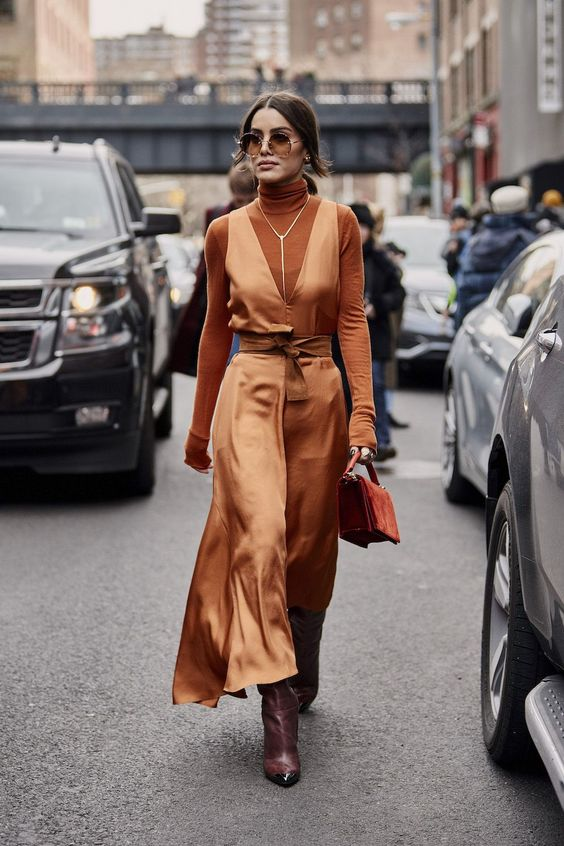 a total rust outfit with a turtleneck, a slip maxi dress, an orange velvet bag, a necklace and purple boots