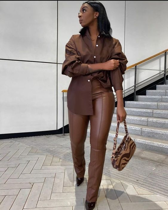 an oversized brown shirt, matching leather pants, black heels and a brown and tan zebra print mini bag