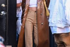 26 Hailey Bieber wearing a white crop top, beige high waisted pants, a brown leather trench, white sneakers