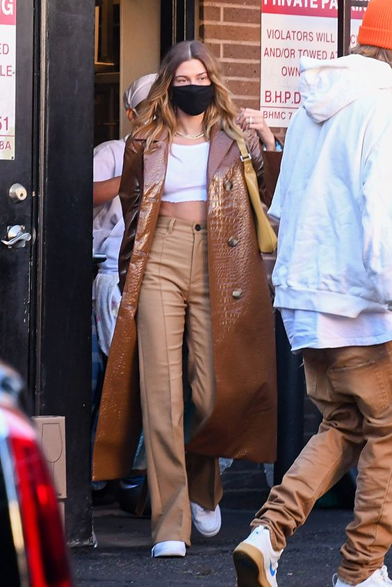 Hailey Bieber wearing a white crop top, beige high waisted pants, a brown leather trench, white sneakers