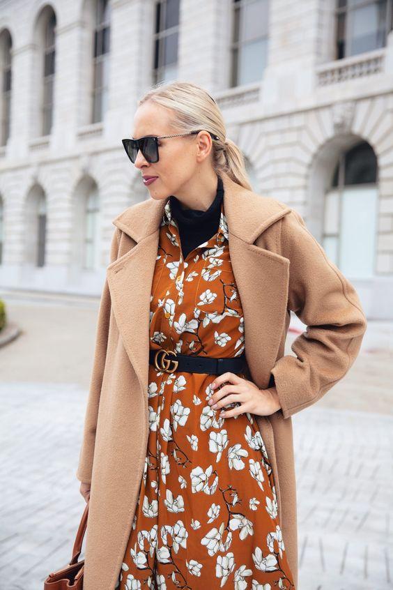 a rust floral dress, a black turtleneck under it, a black belt, a beige coat and a brown bag for a romantic fall look