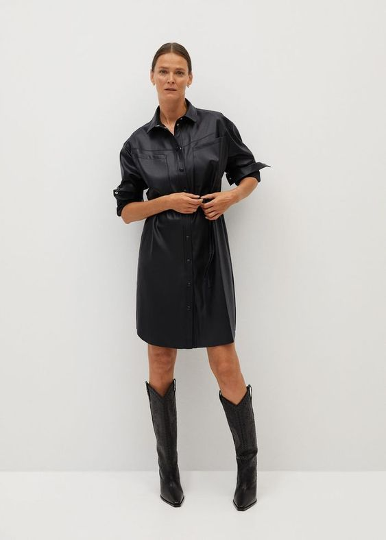 a super trendy fall outfit of a black leather shirtdress over the knee and black cowboy boots is amazing
