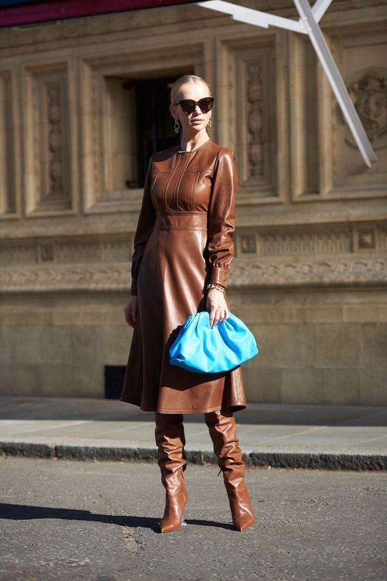 a pretty feminine outfit with a brown leather A-line dress with long sleeves and a high neckline, matching tall boots and a bold blut clutch