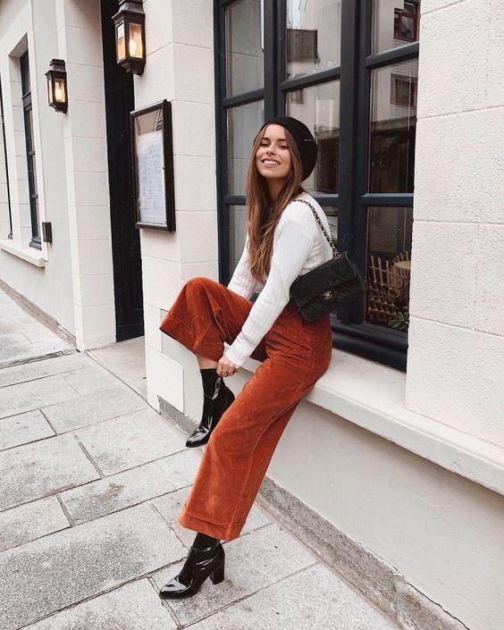 a white jumper, rust corduroy pants, black lacquer boots, a black velvet bag and a black beret for the fall