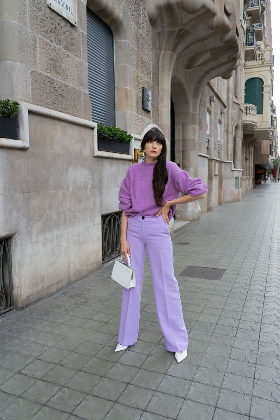 a pastel fall outfit with a purple jumper, lilac trousers, white shoes and a mini bag plus white earrings