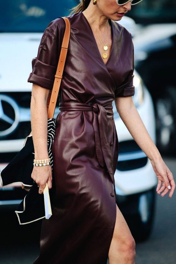 a purple leather midi shirtdress with short sleeves, layered necklaces and a tan bag with a black and white tie