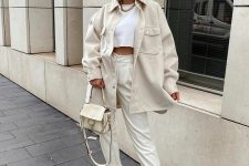28 an all-neutral look with a crop top, trousers, trainers, a shirt jacket and a bag is all you need