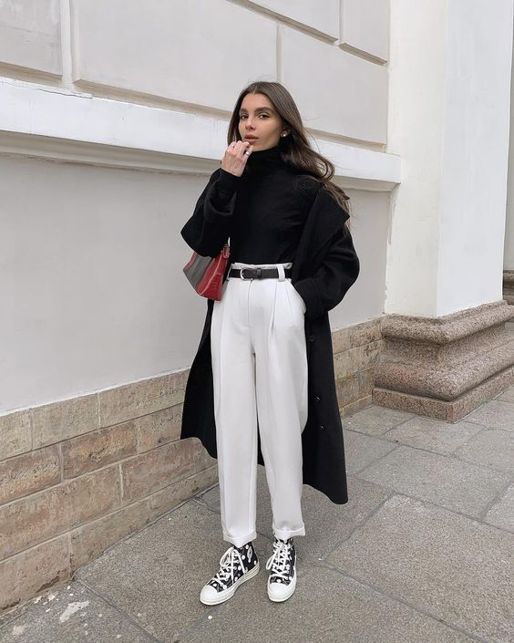 a black turtleneck, white trousers, a black belt and snekaers, a black trench and a bold mini bag for a contrasting look