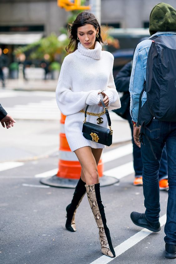 Bella Hadid wearing a white sweater mini dress, two tone boots and a small black bag