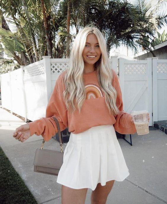 a coral rainbow print sweatshirt, a white tennis skirt, a grey mini bag for a girlish college look