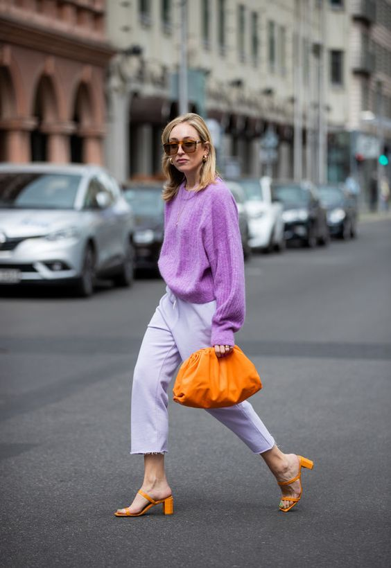 a purple sweater, white trousers, marigold heels and a clutch for a simple and bright fall look