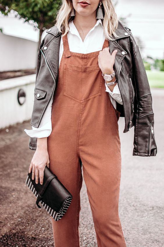 a white shirt, a rust overall, a black leather jacket, a black clutch and tassel earrings for a cute fall look