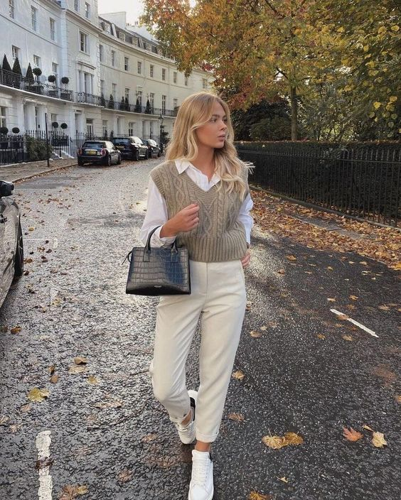 a preppy college look with a white shirt, a grey patterned crop knit vest, creamy pants, white sneakers and a black bag