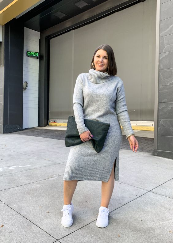 a pretty fall outfit with a grey midi sweater dress, white sneakers, a green clutch and gold hoop earrings for a statement