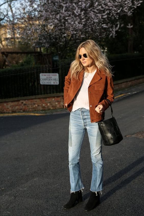 a white t-shirt, light blue jeans, black boots, a black woven bucket bag and a rust-colored jacket for a touch of color