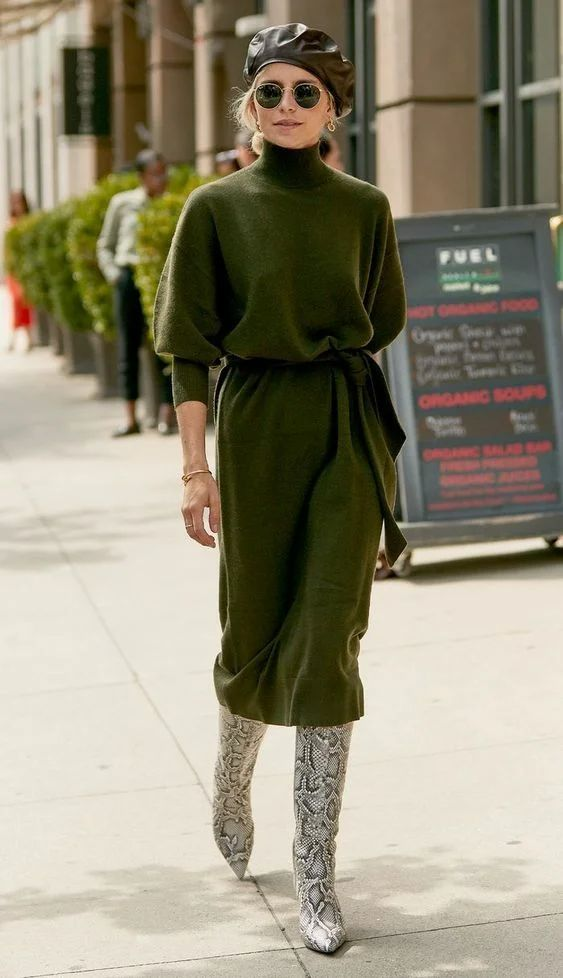 a green turtleneck sweater midi dress with a sash, snakeskin print boots, a black leather beret and statement earrings