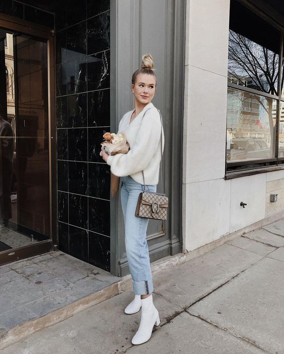 a stylish outfit with a creamy sweater, light blue jeans, creamy boots and a printed bag plus a top knot is awesome