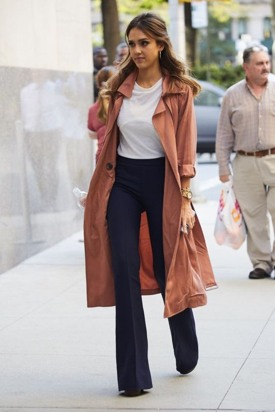 a white t-shirt, navy flare trousers, a rust trench and black boots worn by Jessica Alba