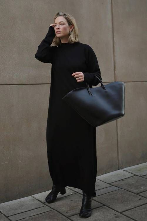 a very simple and comfortable outfit with a black straight maxi sweater dress, black boots and a black tote