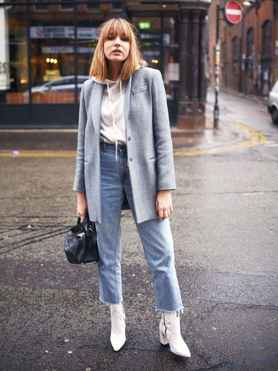 a white hoodie. blue straight jeans, white booties, an oversized grey blazer, a black bag for a stylish fall look