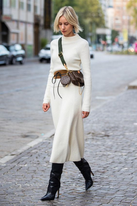 a white sweater midi dress with long sleeves and a high neckline, a brown belt, a brown printed waist bag, black boots