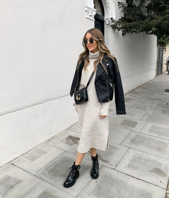 a pretty fall outfit with a neutral turtleneck midi sweater dress, a black moto jacket, black combat boots and a crossbody bag