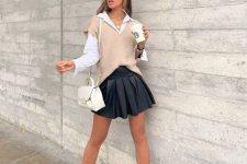 35 a white shirt, a tan knit vest, a black pleated mini, black combat boots and a creamy backpack