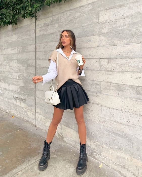 a white shirt, a tan knit vest, a black pleated mini, black combat boots and a creamy backpack