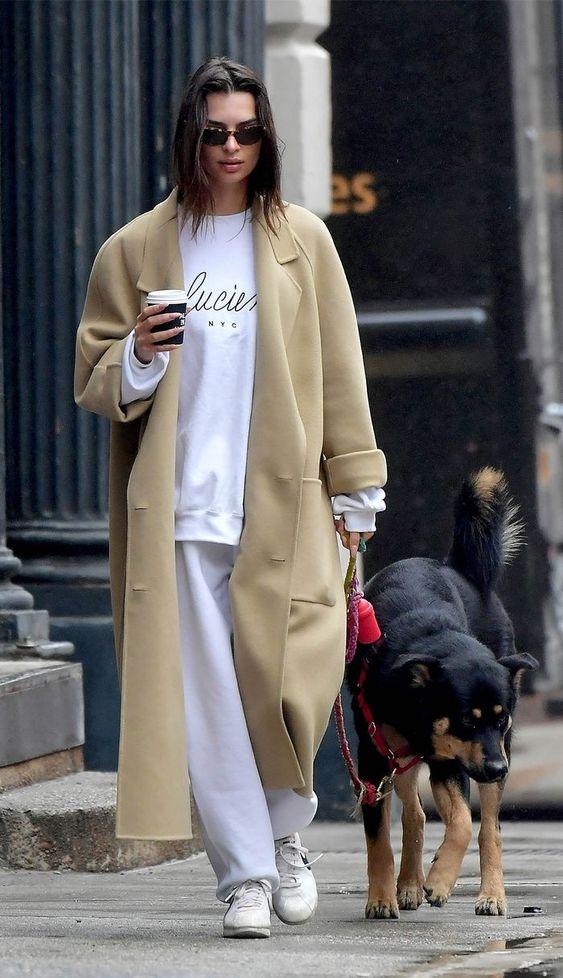Emily Ratajkowski wearing a white sweatshirt, white sweatpants, sneakers, a tan coat looks relaxed