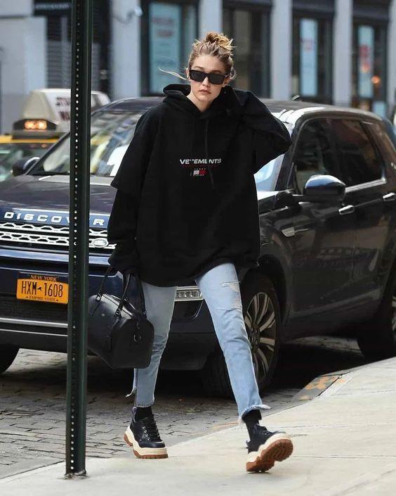 Gigi Haded wearing an oversized black hoodie, light blue jeans, black socks and trainers plus a black bag