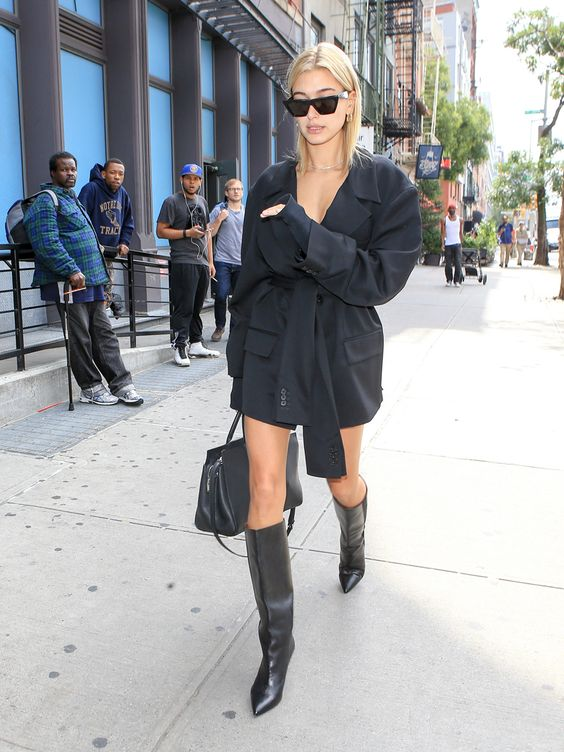 Hailey Bieber wearing a black blazer dress, black knee boots, a black bag for a chic and bold fall look