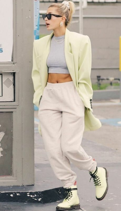 Hailey Bieber wearing a grey crop top, creamy sweatpants, neon green boots and a matching oversized blazer