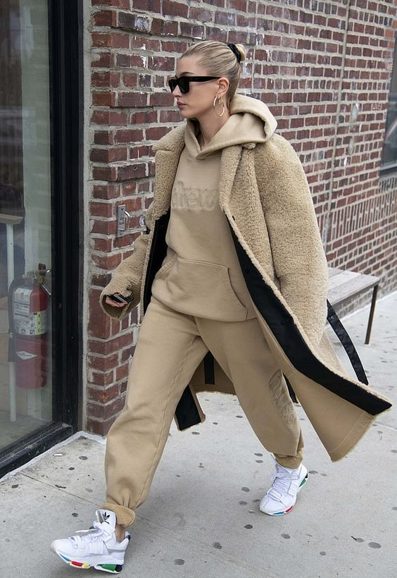 Hailey Bieber wearing a tan oversized hoodie and sweatpants, white trainers and a tan fuzzy coat for winter