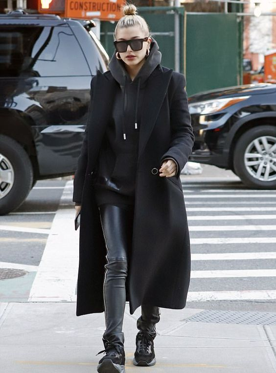 Hailey Bieber wearing a total black look with an oversized hoodie, leather leggings, trainers and a coat plus statement earrings