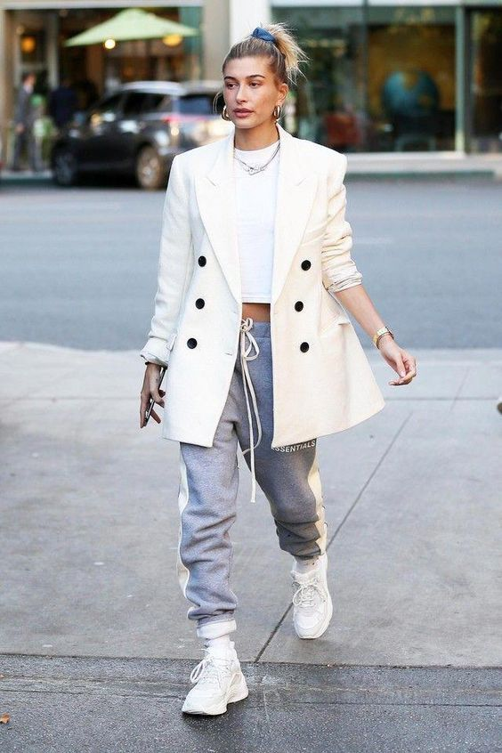 Hailey Bieber wearing a white crop top, grey sweatpants, an oversized creamy blazer with black buttons and white trainers