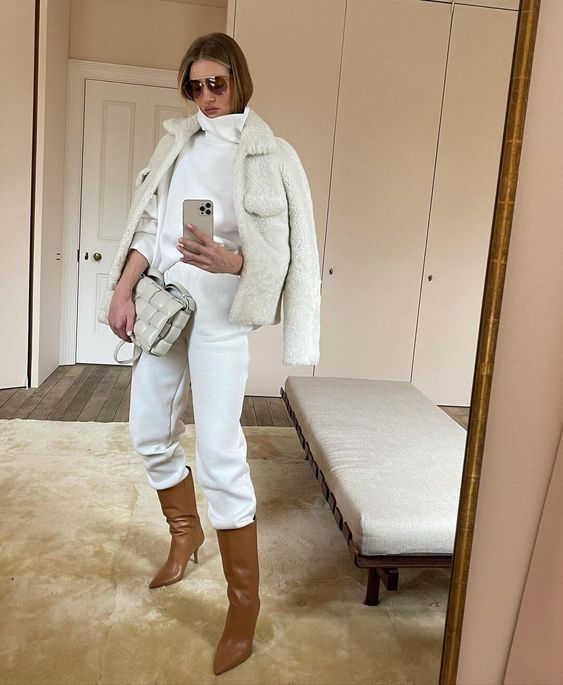 Rosie Huntington-Whiteley wearing a white turtleneck and sweatpants, brown boots, a white faux fur jacket and a creamy bag