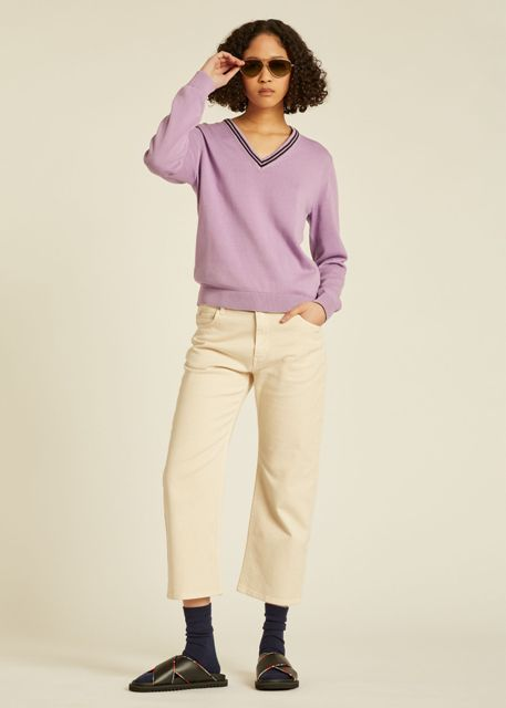 With beige cropped pants, sunglasses and black flat mules