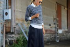 With black pleated knee-length skirt, black pumps and rounded sunglasses