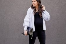 With black shirt, embellished pants, silver chain strap bag and black pumps
