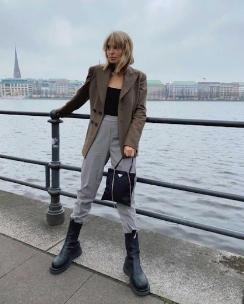 With black top, blazer, gray high-waisted trousers and bag