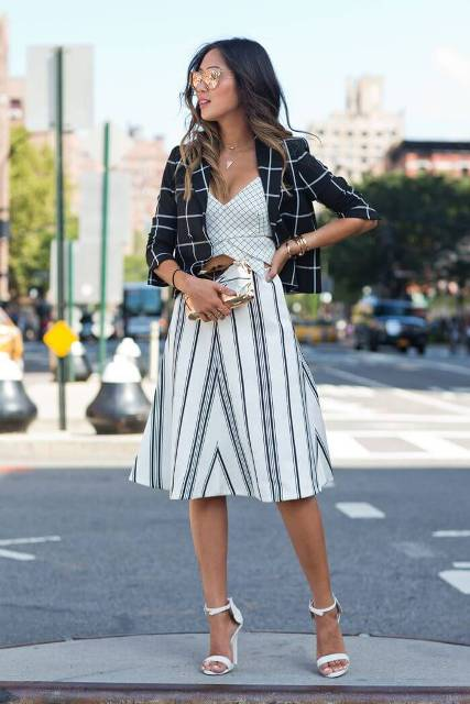 With checked V-neck top, black and white striped A-line knee-length skirt, golden clutch and white ankle strap high heels