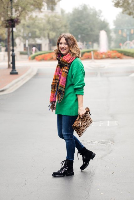 With colorful plaid scarf, green long sweater, jeans and leopard printed clutch